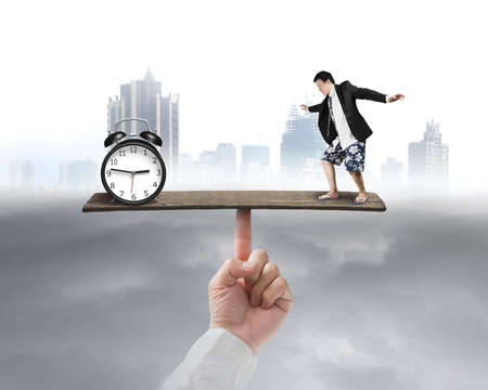 man standing on seesaw vs clock with city background photo
