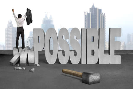bussinessman: cheer bussinessman stand on crushing impossible 3D concrete word with hammer, cement floor, city skyscraper background Stock Photo