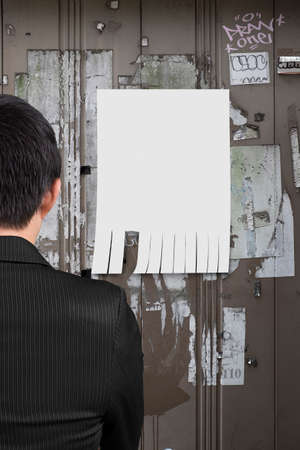 businessman looking at white paper on advertising wall photo