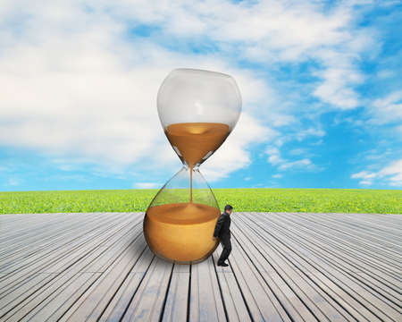 inclined: businessman hand keeping inclined hourglass on wooden floor with nature sky
