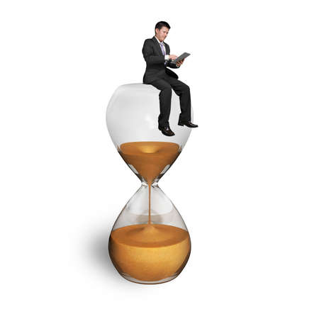 man using tablet and sitting on hourglass with white background photo