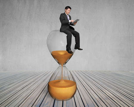 man use smart pad sit on sandglass with concrete wall and wooden floor photo