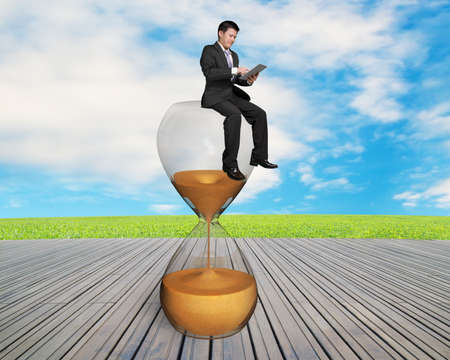 consuming: man using smart pad sitting on sandglass with nature sky and wooden floor