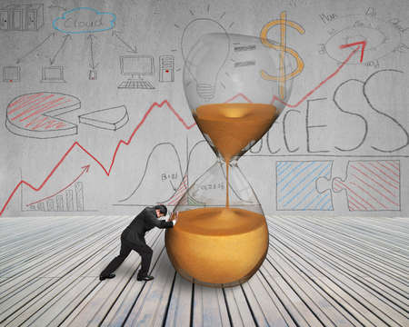 inclined: businessman push inclined hourglass on wooden floor with doodles wall Stock Photo