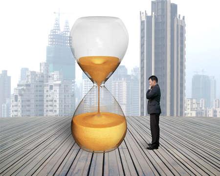 standing businessman looking hourglass with city skyscraper and wooden floor photo