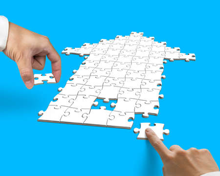 hand with arrow shape puzzle isolated on blue photo