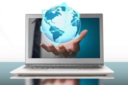 glowing orbit globe in plam through laptop on white background photo