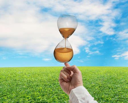 sand clock: indice bilanciamento orologio sabbia con la natura cielo e prato