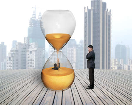 oversee: man oversee businessman flooded in hourglass with city skyscraper and wooden floor