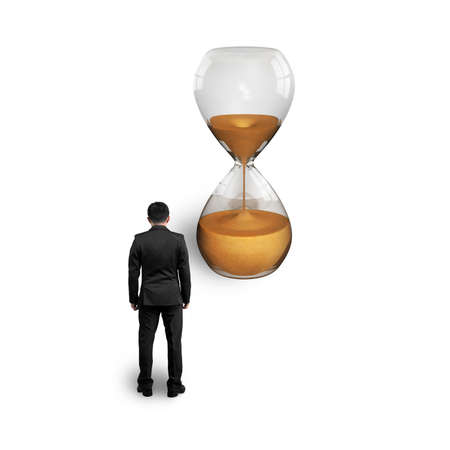 standing businessman thinking and looking at hourglass isolated on white photo