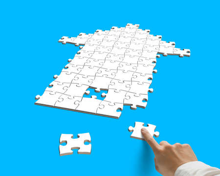 forefinger with puzzles in arrow shape isolated on blue photo