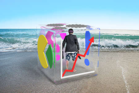 barefoot businessman with shorts standing in glass cube on sea background photo