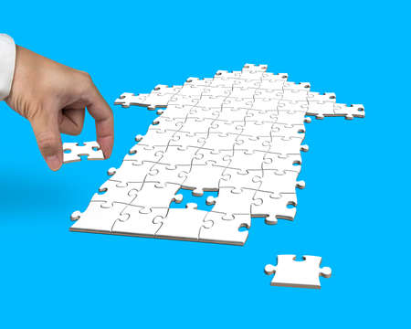 hand with puzzles in arrow shape isolated on blue photo