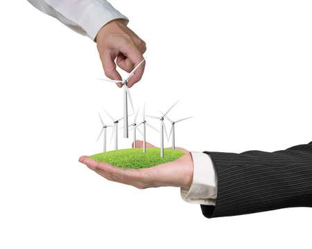 windturbine: men hands holding windturbines on grass isolated on white