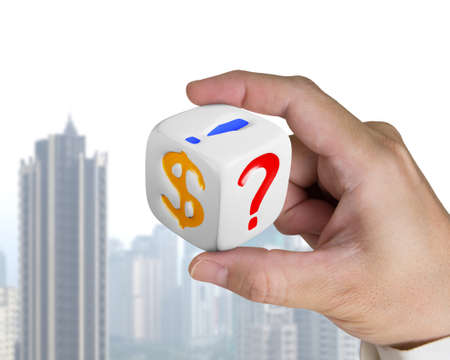 man hand holding white dice with dollar sign on skyscraper background photo