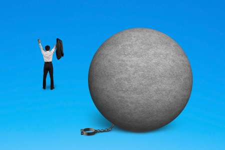 unleash: cheering man free from concrete ball shackle isolated on blue