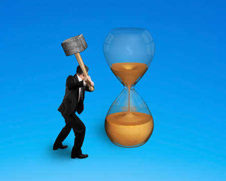 male hand holding hammer to hit hourglass isolated on blue photo