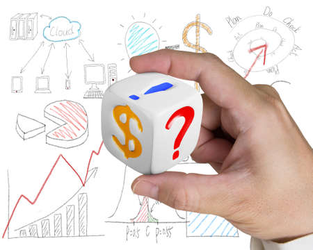 finger holding white dice with dollar sign on doodles background photo