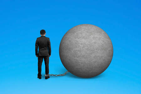 are trapped: man being trapped with concrete ball isolated on blue Stock Photo