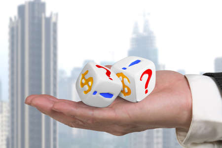 hand giving two white dices with dollar sign and skyscraper background photo