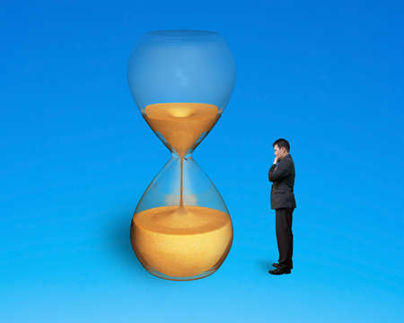 stand man watch hourglass isolated on blue photo