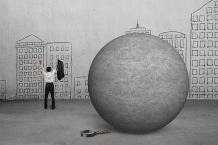 cheering businessman free from concrete ball shackle with doodles wall photo