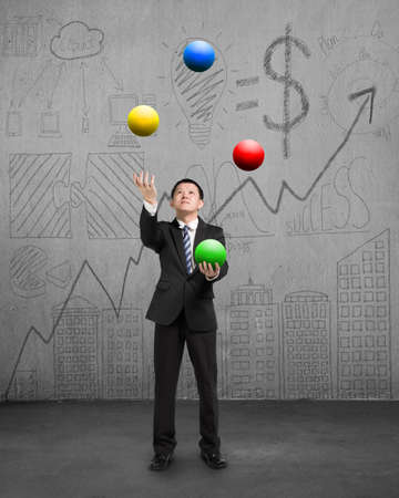 enables: standing businessman playing colorful balls on concrete floor with doodles wall Stock Photo