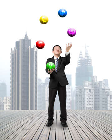 enables: businessman throwing and catching currency symbol balls on wooden floor with cityscape background
