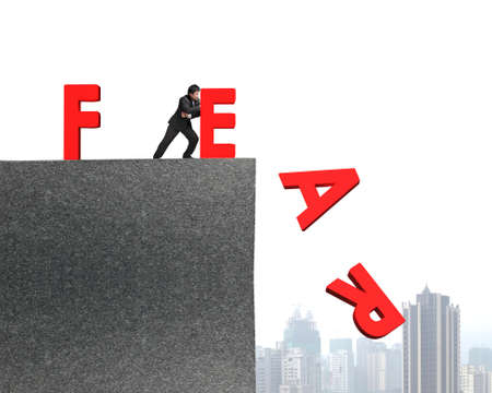 daring: businessman pushing red fear word down on top of concrete building, overcoming fear concept.
