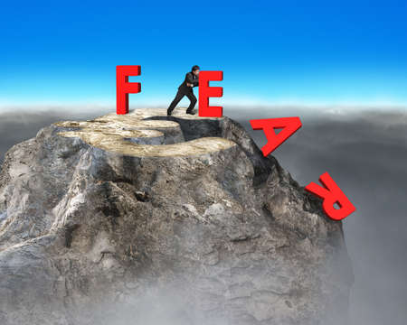businessman pushing red fear word down with euro sign on top of rocky mountain, overcoming fear concept.