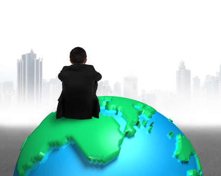 businessman sitting on 3d map globe watching gray buildings cityscape photo