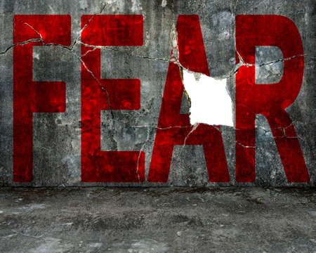red fear word on old mottled concrete wall with large blank hole, overcoming fear concept. Banco de Imagens