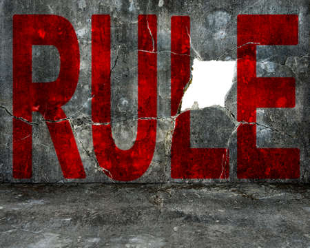 red rule word on old mottled concrete wall with large blank hole photo
