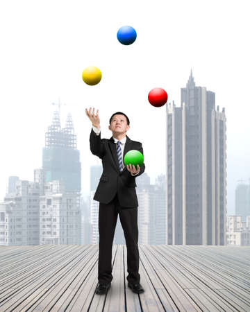 enables: businessman throwing and catching colorful balls on wooden floor with cityscape background Stock Photo
