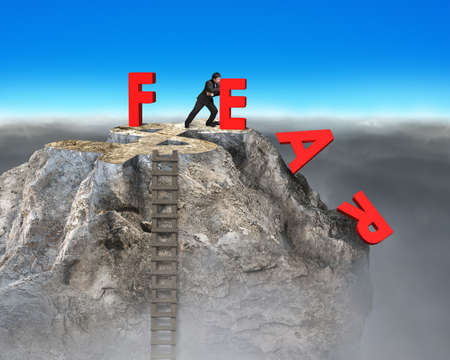 daring: businessman pushing red fear word down with dollar sign and wooden ladder on top of rocky mountain, overcoming fear concept.