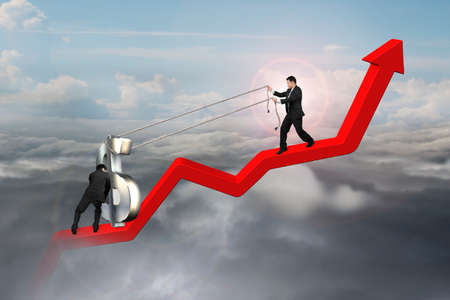 upward struggle: two businessmen moving 3D dollar sign upward on red trend line with sunlight cloudscape background