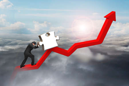 upward struggle: businessman pushing 3D jigsaw puzzle upward on red trend line with cumulus cloudscape background