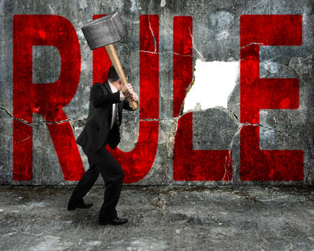 businessman holding sledgehammer hitting red rule word on concrete wall with large blank hole photo