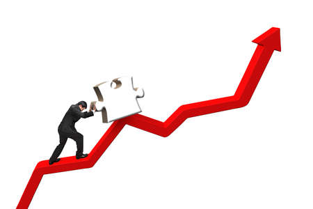upward struggle: businessman pushing heavy jigsaw puzzle upward on red trend line isolated on white background Stock Photo