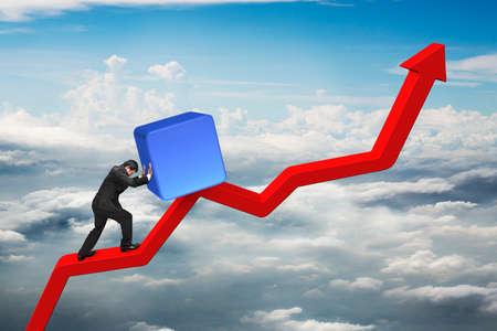 upward struggle: businessman pushing blue 3D block upward on red trend line with cumulus cloudscape background