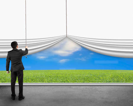 business change: businessman pulling open white blank curtain discovered natural sky meadow on concrete floor Stock Photo