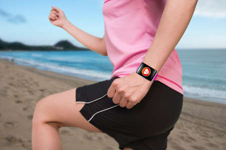 sport female wearing bright pink watchband bent touchscreen smartwatch with red health icon on natural sea beach background