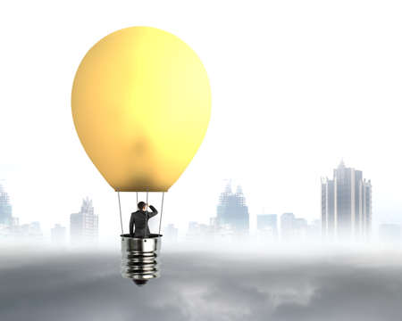 future city: businessman in brightly yellow lamp hot air balloon flying over gray city sky cloudscape background
