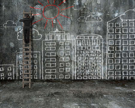 businessman drawing red sun on old mottled concrete wall with city buildings doodles photo