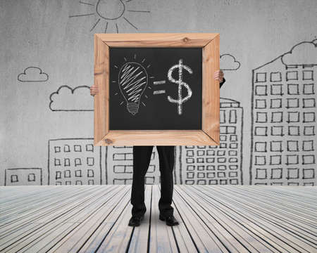 businessman hold blackboard with hand-drawn ideas equal money concept on cityscape doodles concrete wall and wooden floor background photo