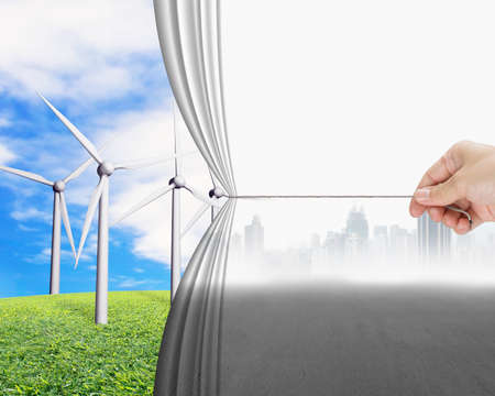 pulling rope: hand pulling gray cityscape curtain revealing group of wind turbines, environmental protection and alternative energy concept Stock Photo