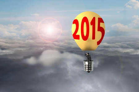 businessman in glowing yellow lightbulb 2015 hot air balloon flying over natural sky daylight cloudscape background