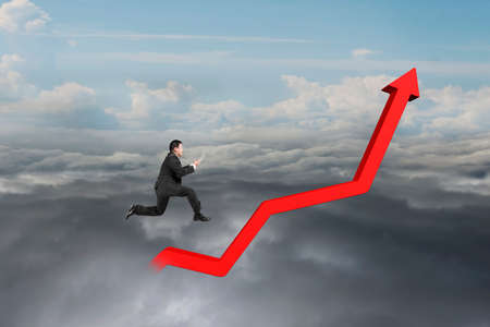 upward struggle: Businessman holding tablet and jumping on red growth trend line with cloudy sky background Stock Photo