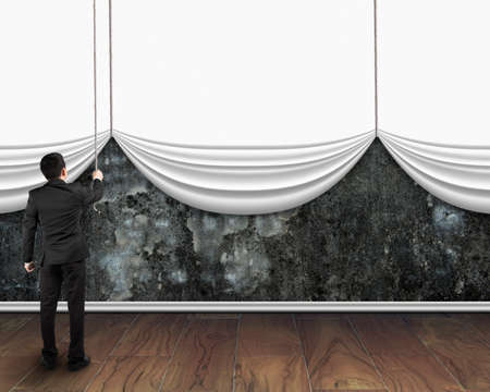 white curtain: businessman pull open blank white curtain covered old dirty concrete wall on wooden floor background Stock Photo
