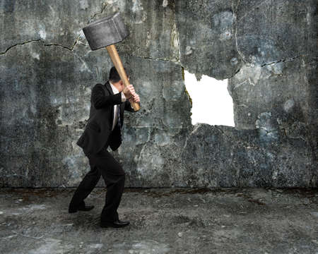 overcome a challenge: businessman hold sledgehammer cracking big white hole on concrete wall background